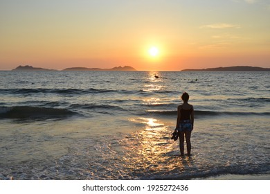Silhouette of a woman looking the sunset at the beach