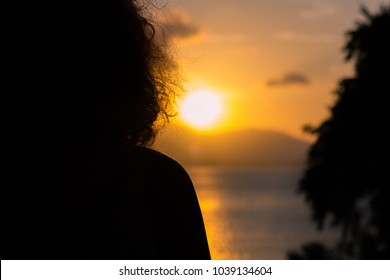 Silhouette woman looking to sunset on island with overexposed sun