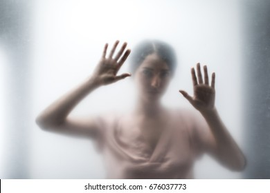 Silhouette of woman looking through the glass and touching it with hands