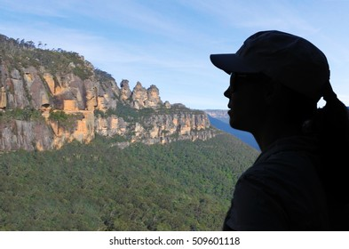 Silhouette of a woman looks at the Three Siaters rock formation in the rainforest of Jamison Valley at the Blue Mountains in New South Wales, Australia.