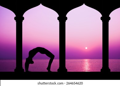 Silhouette of woman making yoga in sunset, staying in temple near the sea