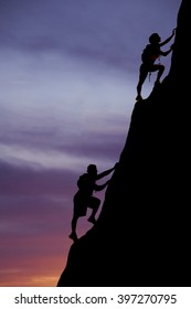 A silhouette of a woman and man climbing up a mountain with packs on their backs.