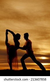 a silhouette of a woman and man dancing in the outdoors.