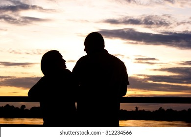 Silhouette of woman with man see beautiful sunset near the river.