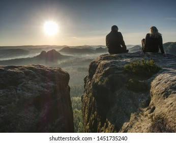 Silhouette woman and man shooting sunset on the top mountain. Relax time travel on holiday