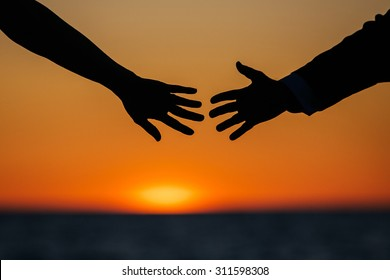 Silhouette of a woman and a man's arm, which extends opposite each other, sunset in the background.