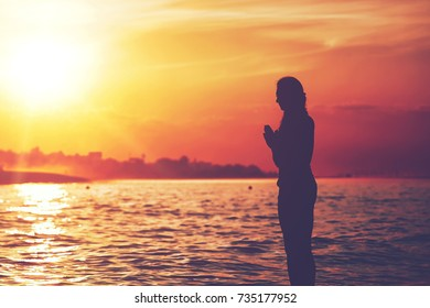 Silhouette of woman meditating yoga on paddle surf board at beautiful sunset
