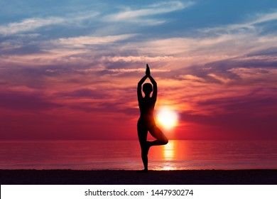 Silhouette of Woman Meditating in Yoga pose by the Sea at Sunset. Nature Meditation Concept. Low key photo. relax time