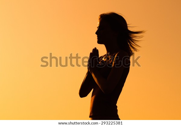 Silhouette of a woman meditating.Peace of mind