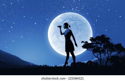 Silhouette of woman at night looking in binoculars