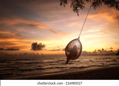 Silhouette woman on a beach swing