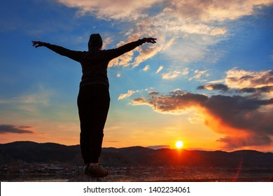 silhouette of a woman on a cliff at sunset