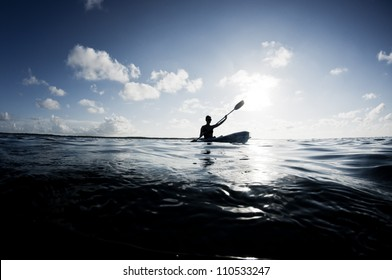 Silhouette of woman on ocean kayak
