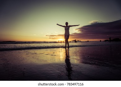 Silhouette of woman on sunset beach, girl with open arms over sea coast. Freedom concept