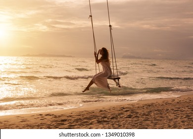 Silhouette of woman on swing above sea shore on sunset