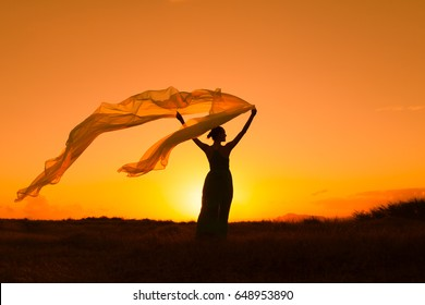 Silhouette of woman outdoors holding fabric blowing in the wind.