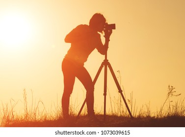 Silhouette of woman photographer shooting landscape with camera on tripod at sunset time in the field
