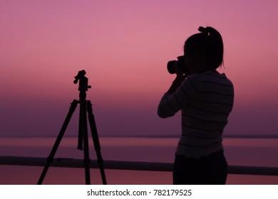 Silhouette woman photographer shooting sunset,Silhouette photographer with sunset