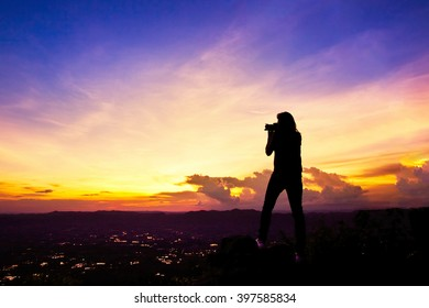 Silhouette of woman photographer take landscape photo on high mountain at twilight.