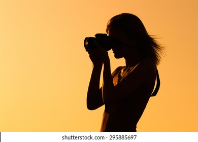 Silhouette of a woman photographing. Woman photographing