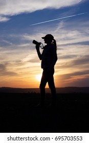 Silhouette Woman Photographing Landscape At Sunset. Female photographer holding a camera.