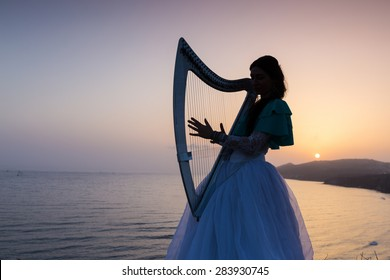 Silhouette woman plays harp by the sea at sunset in Santorini, Greece