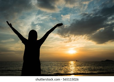 silhouette of woman pointing with finger in sky on the beach