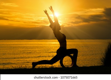 Silhouette of woman practicing warrior one pose yoga on the beach at sunset