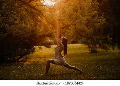 Silhouette woman practicing yoga in the forest at sunset. Meditation workout concept.
