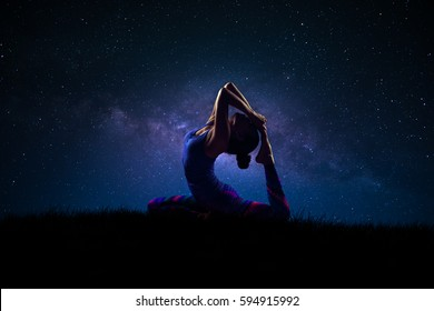 Silhouette of a woman practicing yoga with milky way night sky in background