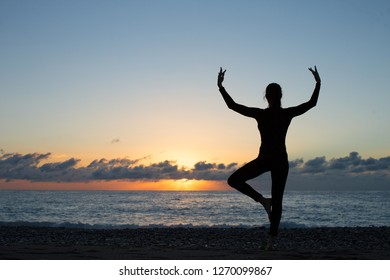 silhouette of woman practicing yoga on the beach at sunset, tree pose, peace and inner calmness concept