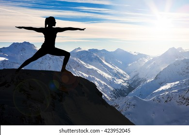 Silhouette Of A Woman Practicing Yoga On A Cliff Against Snowy Mountains