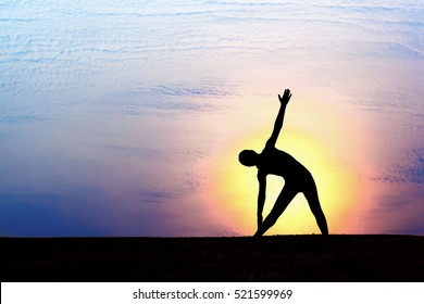 Silhouette of woman practicing yoga at sunrise