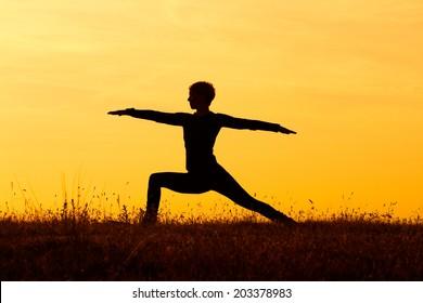 A silhouette of a woman practicing yoga,Yoga-Virabhadrasana /Warrior pose