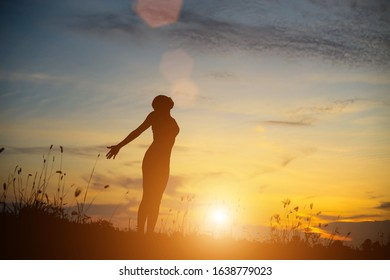Silhouette of woman praying over beautiful sky background