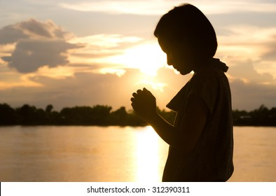 Silhouette of woman praying over beautiful sunset background.
