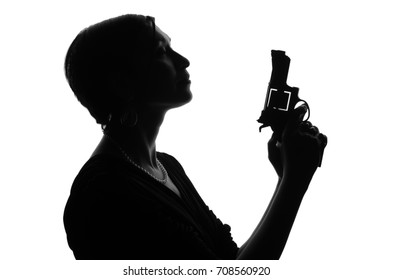 Silhouette of woman private detective with gun in her hand. Criminal scene. Studio shot