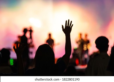 Silhouette woman raised hand to worship God over blurred Sunday service in church background