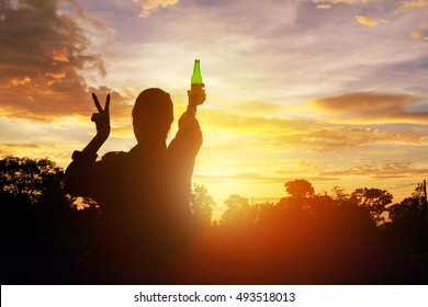 Silhouette woman raised hands holding a green beer bottle on the sunset sky,