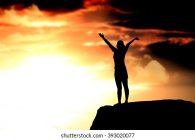 silhouette of woman with raised hands on the beach at sunset