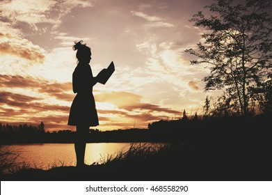 Silhouette of woman reading book at sunset sky