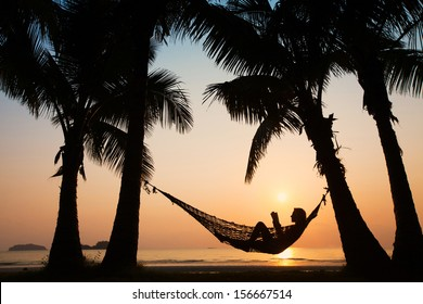 silhouette of woman relaxing in hammock with the book