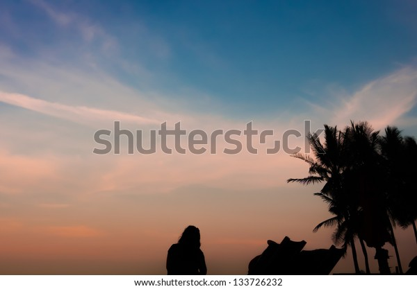 silhouette woman relaxing on the sunset beach view with beach chair and coconut tree in scene