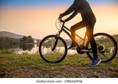 Silhouette of a woman rides a bike at beautiful landscape on sunset.Orange-blue sky background. - Image