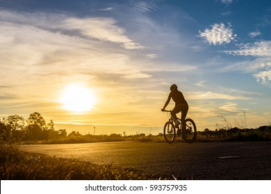 Silhouette of a woman rides a bike at sunset.Orange-blue sky background.