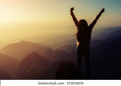 silhouette woman rising hands on mountain in morning with vintage light