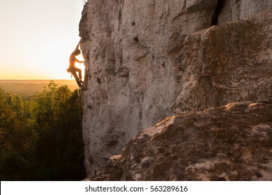 A Silhouette of a Woman rock climbing on Ontario's Niagara Escarpment in Canada