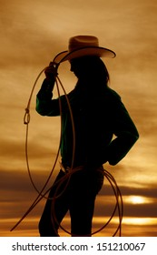 A silhouette of a woman with a rope and cowgirl hat, with a beautiful sunset in the background.