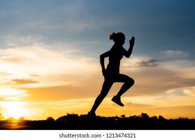 silhouette woman running alone at beautiful sunset in the park.