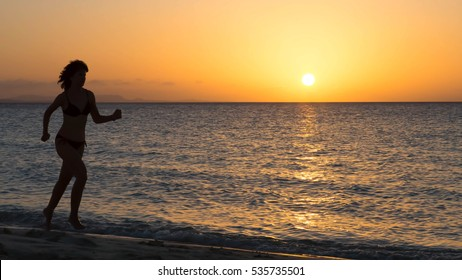 Silhouette of a woman running along a beach at sunset with copy space.